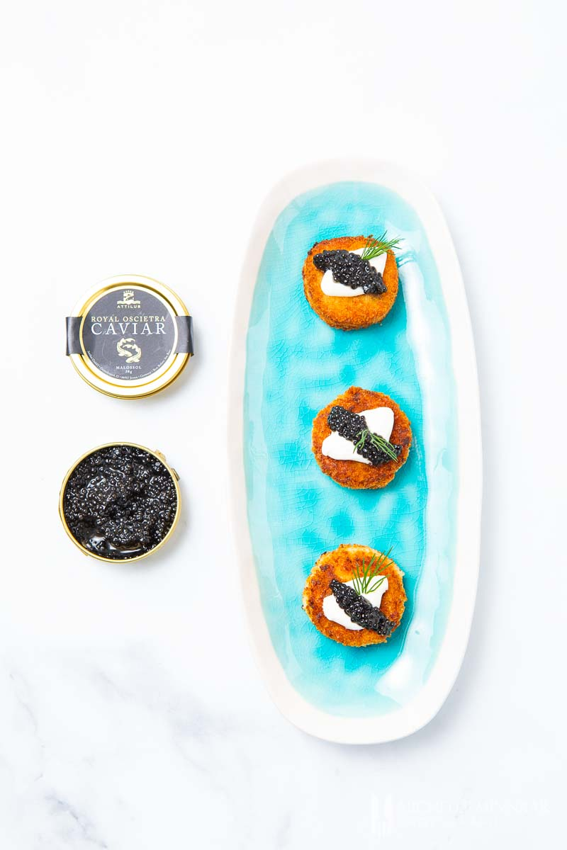 A plate of three salmon rissoles with a can of caviar