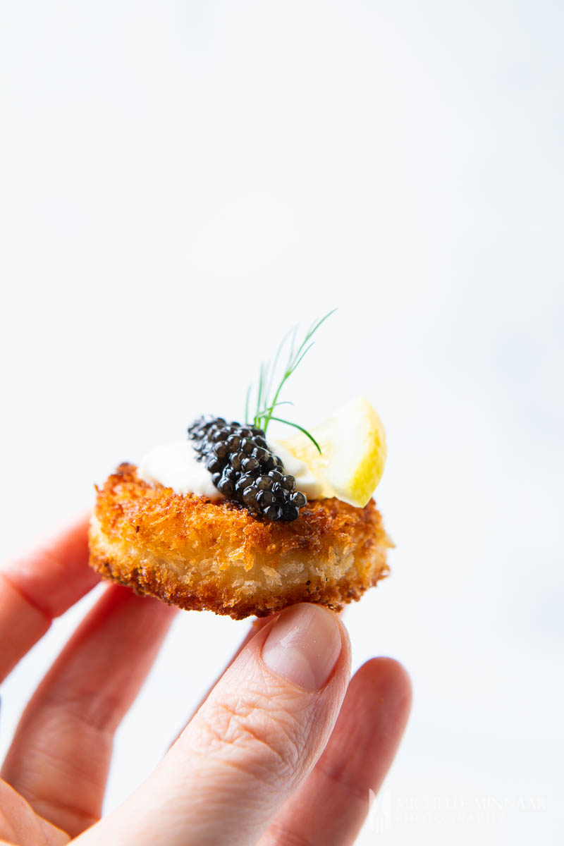 A close up of a fried canape with caviar on it