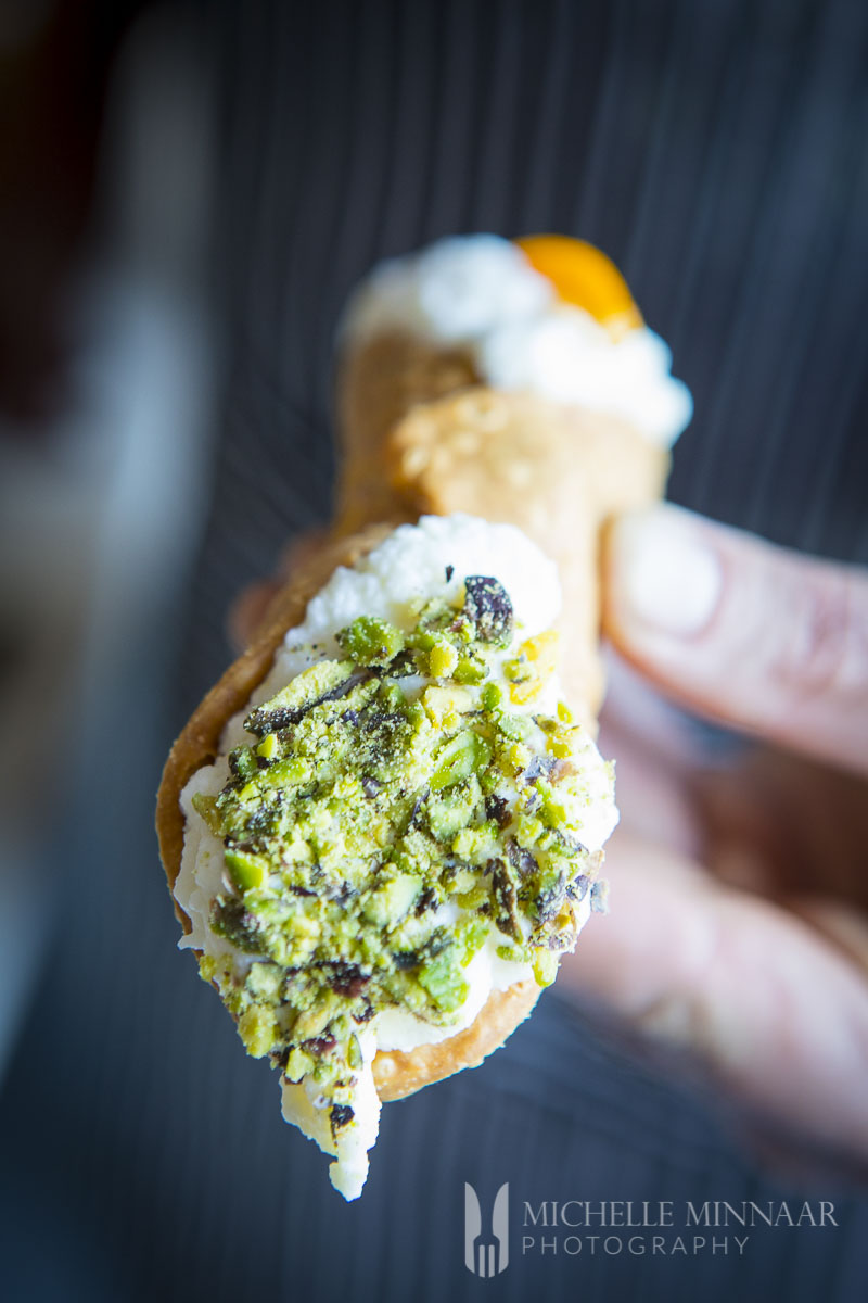A cannoli with a pistachio tip