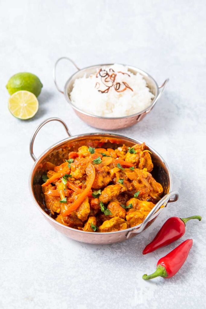 Bowl of Chicken Jalfrezi, white rice, whole lime and whole red peppers