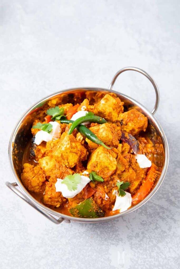 A bowl of orange tawa paneer tikka